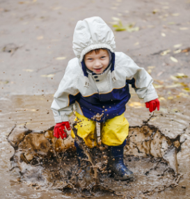 Happy child jumping on puddles in rubber boots